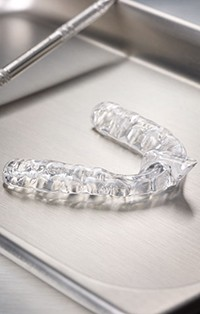 Teeth grinding oral appliance on metal tray