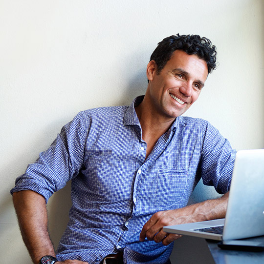 Man with attractive smile sitting at desk with laptop