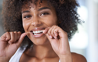 Woman with healthy smile flossing