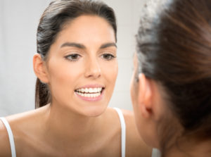 woman looking at healthy teeth and gums in mirror