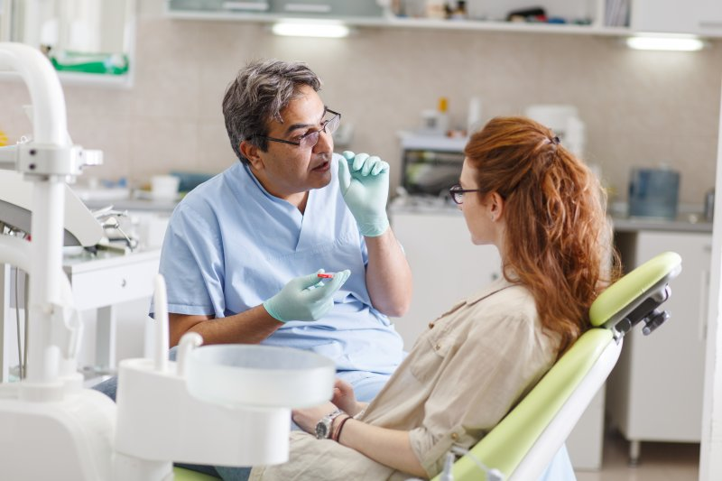 a woman sitting and talking with her dentist